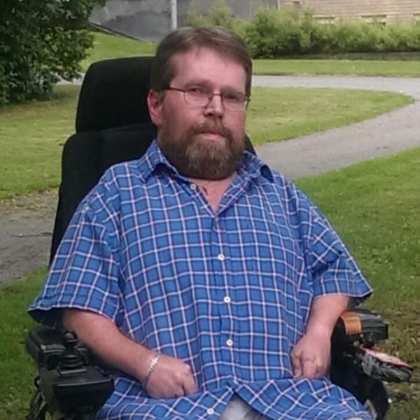 En skäggig man i Permobil med rutig blå skjorta sitter i en park på gräsmattan..