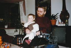 Jag sitter i rullstol med mitt barn i knät som äter godis. Bakom ser man fönster och prydnadsaker och en tv.